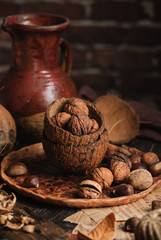 Fresh organic walnuts, coconuts and chestnuts on a wooden brown rustic background. Autumn still life. Close up