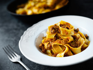 rustic italian pappardelle bolognese pasta in meat sauce