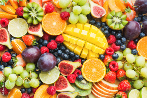 Wall mural Assortment of healthy raw fruits and berries platter background, strawberries raspberries oranges plums apples kiwis grapes blueberries, mango, top view, selective focus
