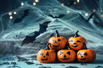 Halloween decoration with funny pumpkin heads, spider, web and flying bat on mystical bokeh background.