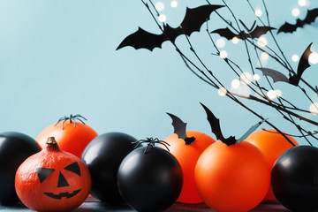 Halloween card with funny pumpkin head, flying bat, black and orange balloons on turquoise background.