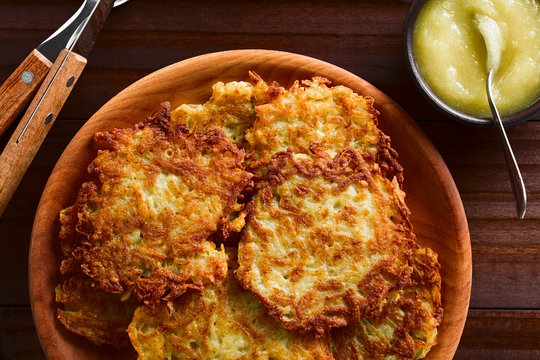 Fresh homemade potato fritters or pancakes on wooden plate with apple sauce on the side, a traditional German snack or dish called Kartoffelpuffer or Reibekuchen, photographed overhead on dark wood
