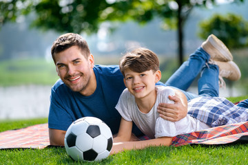 Father and son, lying together on a picnic blanket with ball, outdoors