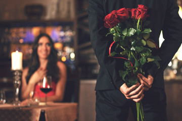 Fototapeta Romantic surprise concept - a man holding a bouquet of roses and wants to give it to a woman during dinner at a restaurant. obraz