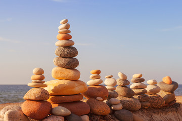 Stones balance in the evening sun on the beach. Concept of harmony, balance and meditation
