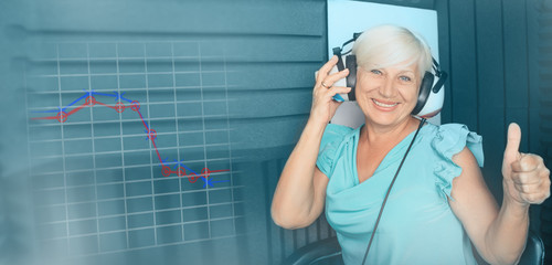 Senior woman getting a hearing test at special audio room, holographic audiogram on the background. Audiometry, hearing test