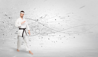 Young karate trainer doing karate tricks with chaotic concept