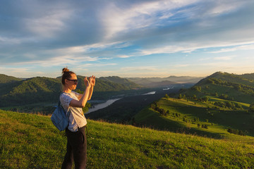 Woman taking photo on mobile phone at the mountain peak.