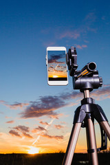 Smartphone on tripod capturing image of sundown in vertical mode