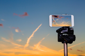 Smartphone on tripod capturing image of stunning sundown