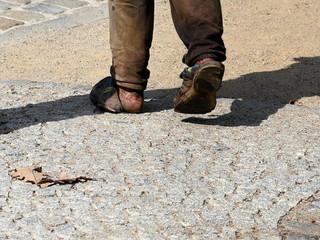Obdachloser mit nackten Füßen in kaputten Schuhen