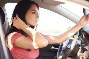Shot of beautiful brunette woman dressed in casual t shirt, looks seriously at mirror of car, has thoughtful expression, concenrated into distance. Horizontal view of gorgeous lady in automobile