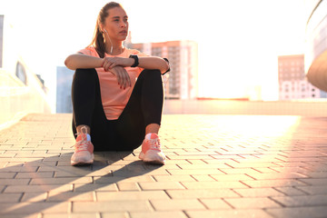 Young attractive sporty girl resting on the street with mobile phone and music, outdoor at sunset or sunrise in city.