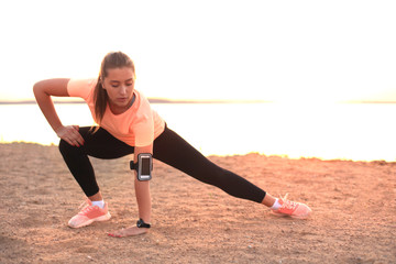 Young attractive sporty fitness stretching legs, on the beach outdoors at sunset or sunrise.