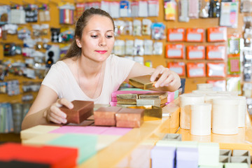 Smiling girl is choosing small boxes for gifts