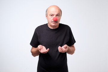 Portrait of unhappy man with a red nose celebrating all fools day. He is sad and depressed