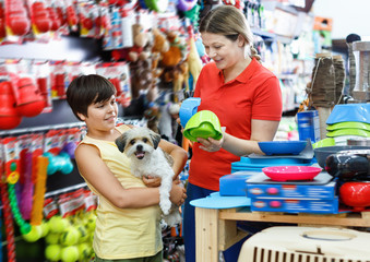 Happy teen boy with mother visiting pet shop in search of accessories for their dog