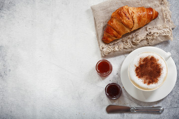 Cup of cappuccino coffee with croissant