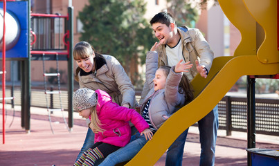Happy family at sliding board outdoors .