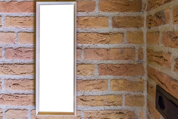 empty small long rectangular picture frame hanging on a brick wall close to a corner