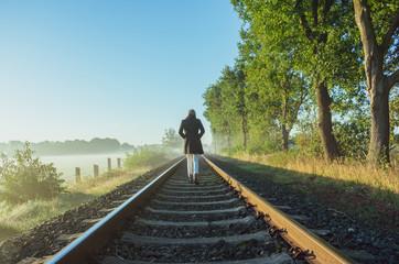 Einzelne Frau läuft auf Bahnschienen dem Horizont entgegen.