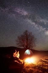 Camping night in mountains. Couple hikers man and woman resting near burning campfire under starry sky, Milky way. Illuminated tent, big tree and distant hills on background. Outdoor activity concept