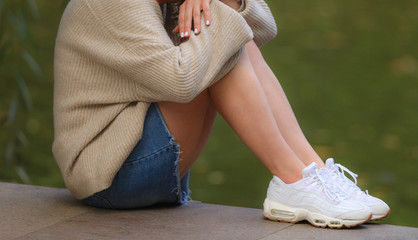 legs of a sitting girl in a short skirt