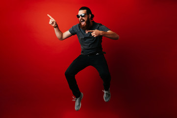 Amazed bearded hipster man wearing sunglasses and jumping over red background and pointing away