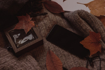 Black mobile phone with wooden perfume on the sweaters