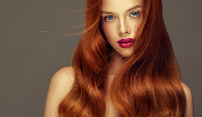 Red head girl with long  and   shiny curly hair .  Beautiful  model woman  with wavy  hairstyle. Care , cosmetic and beauty products