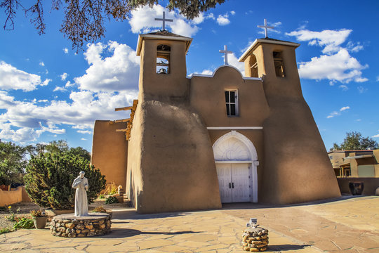 Historic adobe San Francisco de Asis Mission Church in Taos New Mexico in dramatic late afternoon light under intense blue sky with fluffy while clouds and birds in the belfry