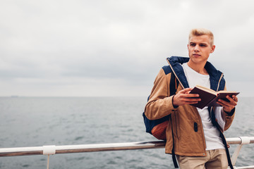 College student with backpack reading book by sea on pier in Odessa on rainy autumn day
