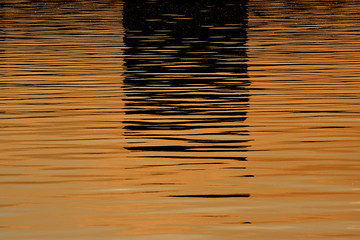 Beautiful reflections on the water before sunset in orange and dark colors  – background image, Moscow river, Russia