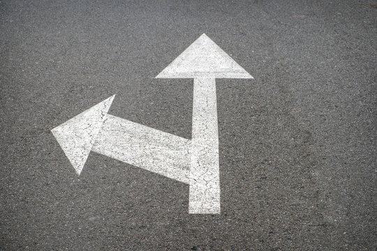 white arrows on asphalt road - street arrow