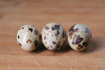 Three quail eggs on wooden background , small copyspace