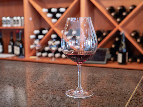 Small tasting glass of red wine on bar counter