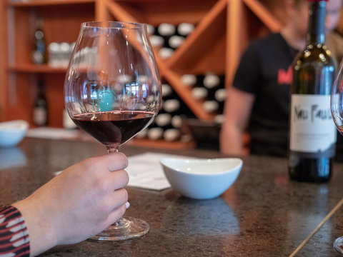 Womans hand holding a tasting glass of red wine at tasting room