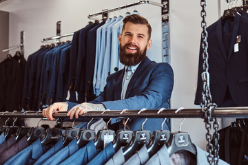 Smiling tattoed male with stylish beard and hair dressed in elegant suit standing in a menswear store.