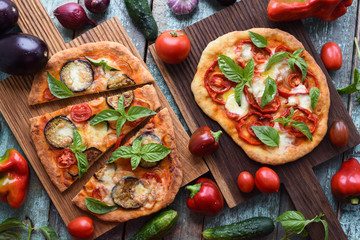 Healthy vegetarian food. Rustic pizzas with eggplants, tomatoes and bell peppers on oak cutting boards served with raw ingredients