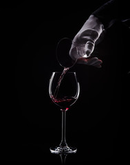 Hand pour red wine from decanter to glass