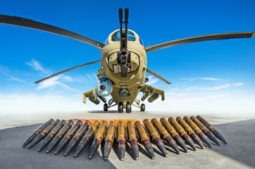 Military helicopter is parked, in the foreground the cartridges are the weapons that it shoots.