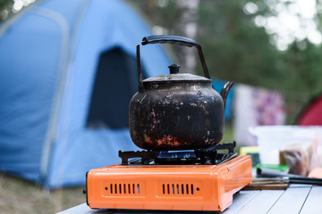 Iron burnt teapot on a gas burner on the background of a tent in nature, breakfast at the camping
