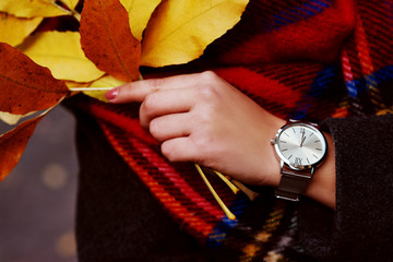 Street fashion details: close up of silver wrist watch. Model wearing gray coat, trendy red tartan scarf, holding yellow autumn leaves. Copy, empty space for text