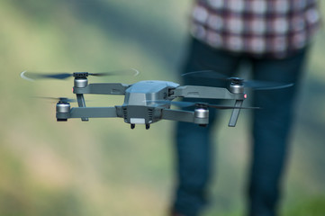 closeup of small drone for video application in outdoor with pilot on background