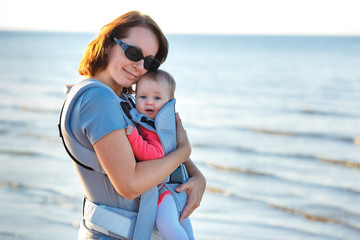 Baby and mother on sea at summer day. Child in a carrier backpack
