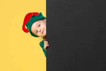 Little girl in a Christmas elf costume on a yellow background. A child looks out from behind a black sheet. Festive photo with place for text. Wall mural
