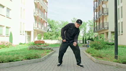 A young man dressed in black breakdancing in the street. Long shot