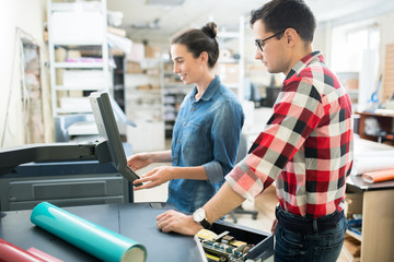 Papier Peint - Smiling attractive young lady in casual shirt viewing information on monitor of printer while choosing print options with colleague in printing house