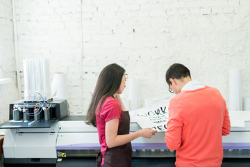Papier Peint - Rear view of busy printing specialists examining banner with text and standing at large format printer in office