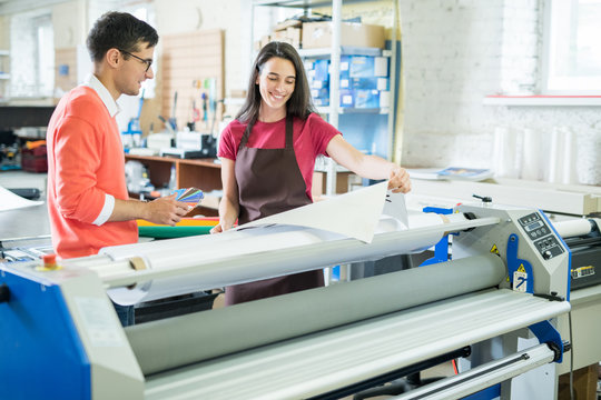 Cheerful excited beautiful lady in apron showing printed banner to manager who picking out color on swatch for printing